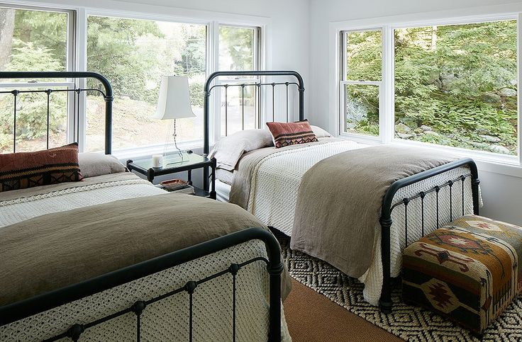 "The twin guest rooms were designed to be durable and low maintenance. ""Anyone could come in there after a day on the lake and not feel like they're ruining anything,"" Nicole says. Cozy knit blankets and pillows made with vintage textiles warm up the iron beds. The designer used a ""completely foolproof"" jute rug on the floor."