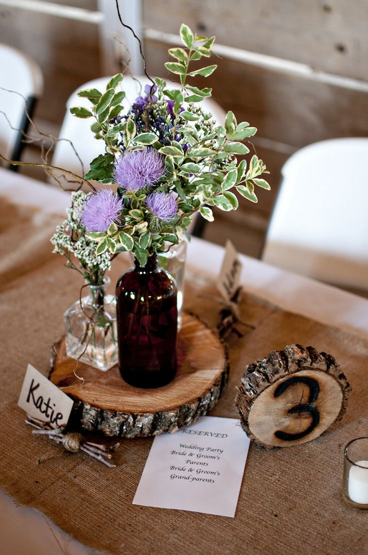 small tree slices are branded with the table numbers for a rustic reception - thereddirtbride.com -see more of this wedding here