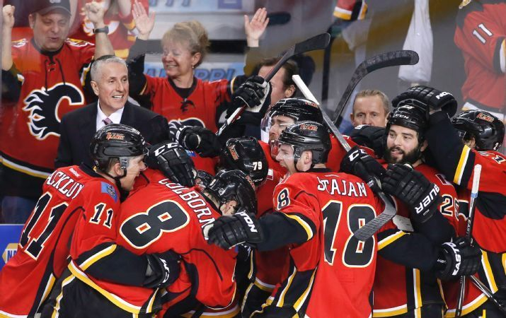 Calgary Flames coach Bob Hartley, top left, watches players celebrate after an empty-net goal and 3-1 victory over the Los Angeles Kings during the third period of an NHL hockey game Thursday, April 9, 2015, in Calgary, Alberta. The Flames clinched a playoff berth. (AP Photo/The Canadian Press, Larry MacDougal)