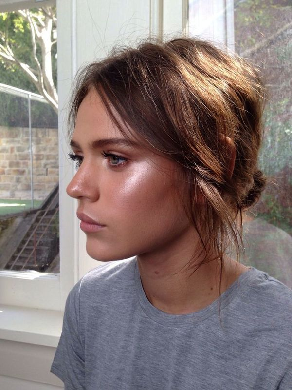 Natural makeup with highlighted cheekbones and pink blush. Messy low bun hair.
