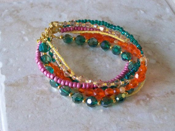 This 6 Strand Beaded Bracelet is made of Green and Orange Crystals and Pink and Yellow seed beads. This beautiful bracelet has a sliding 3-loop