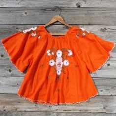 Burnt orange (THE colour of the 70's, it was literally everywhere: kitchen benches, bathrooms, wallpaper, decorative items) ladies hippy top with white flower design.