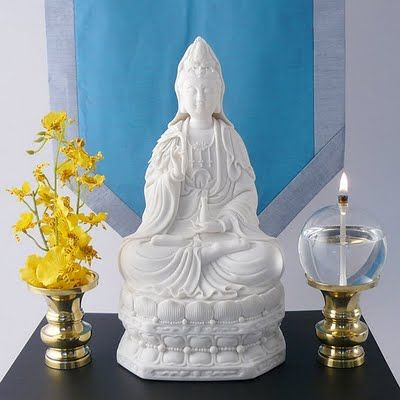 Simple Meditation Altar; flowers, statue, and oil lamp on a small table with a calming blue wall hanging as a backdrop.