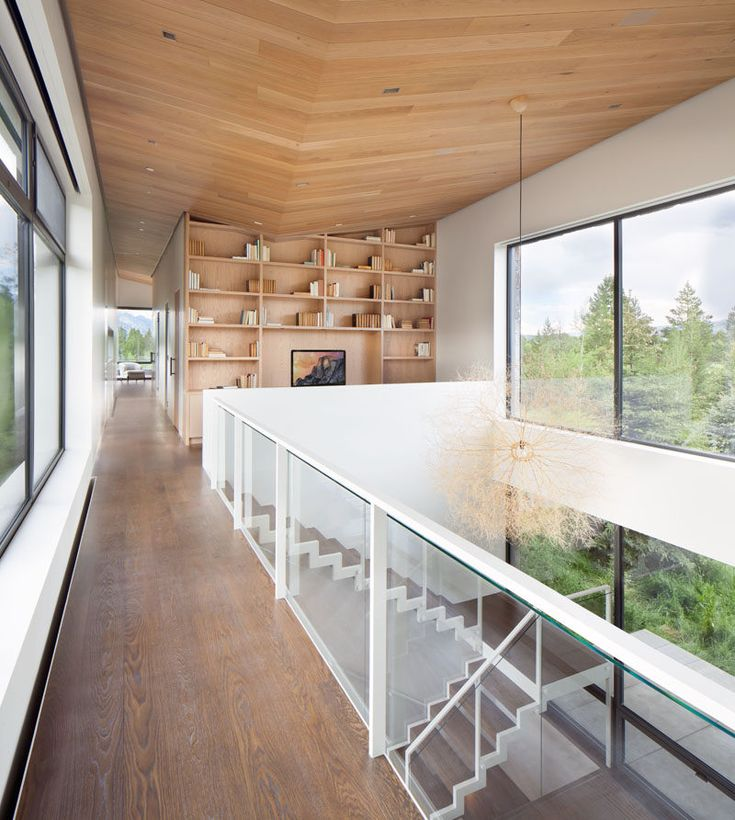 Stairs lead to the upper floor of this modern house, and a large double-height space allows the natural light from the windows to flood the interior. At the top of the stairs there's a small library area with a built-in bookcase. #Stairs #Shelving #WoodCeiling
