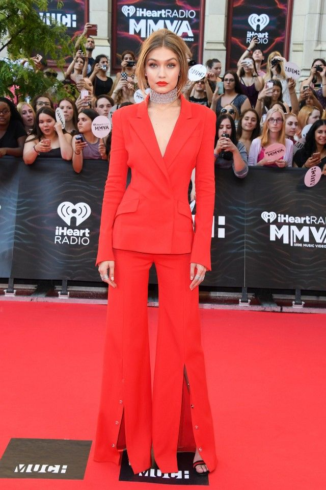 Host, Gigi Hadid, walks the red carpet at the MMVA's in a redThierry Mugler suit.