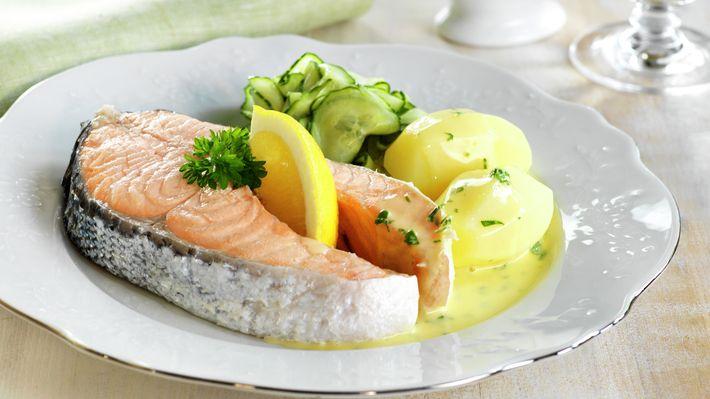 Traditional salmon dinner dish - Kokt laks er en rotekte norsk middagsklassiker. Retten er festmat og har blitt selve middagsbordets symbol for 17. mai i Norge. Med fiskeskivens vakre korallrøde farge blir den også en fryd for øyet der den ligger side om side med agurksalat, poteter og gyllent sandefjordsmør.
