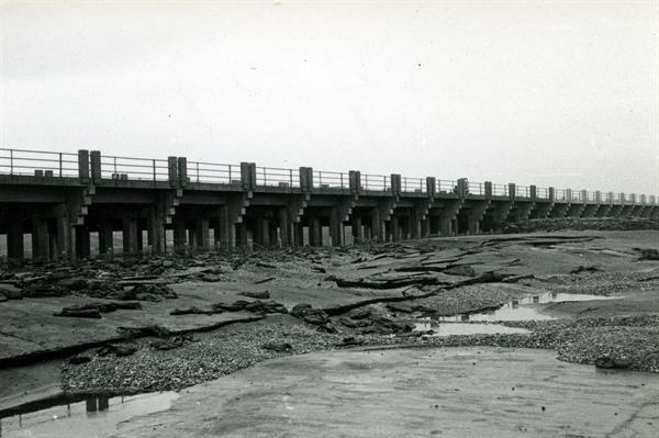 Overlaat groene rivier Arnhem - Zuid. Als gevolg v.h. Overstortende water is de bekleding van 't Zandasfalt (0% intumen door overdrukteen bij de naden opengebassten en in het onderliggende zand uitgespoeld, waarna de dijk op een plaats is bezweken. Oorzaak geen, drainage aan de benedenstroomse zijde nabij te tien. Historisch archief van periode 1900-1960.