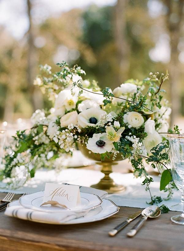 Low Wedding Centerpieces: Create a short, elegant table decoration using a vase that doesn't perch your wedding flower arrangements too high. These creamy anemones and ranunculus flowers pair well with this sophisticated brass example.