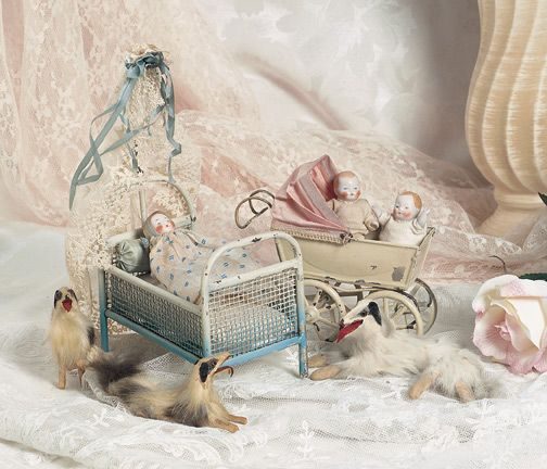 """Group, German All Bisque Babies and Accessories Each 2 1/2"""" (6 cm). Each baby is pink tinted bisque with painted tan baby hair and facial features, jointed bisque limbs. Included are two babies, metal bed (probably Maerklin) with canopy, tin baby carriage with original rose cotton sunshade, and a family of three fur and paper mache dogs. Circa 1920."""