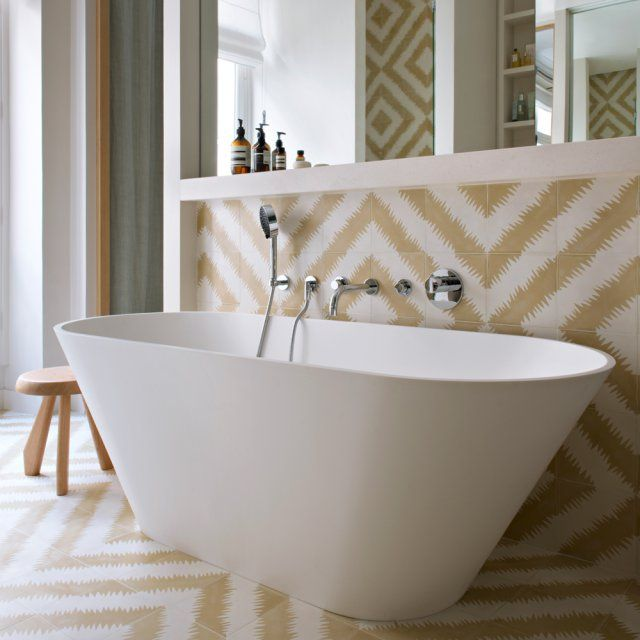 """Une salle de bains pastel. Grand calm dans la salle de bains attenante à la chambre, entièrement habillée de carreaux """"ZigZag"""", Popham. Baignoire """"Barcelona"""" en Krion, Riho. Robinetterie, Dornbracht. Tabouret, Charlotte Perriand, Cassina."""