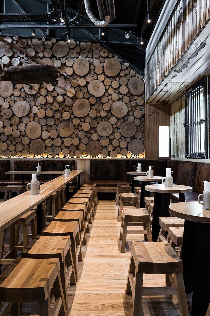 the wall of logs in this beerhall is meant resemble a forest floor - Wood Wall Design Ideas