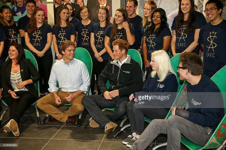 Britain's Prince Harry sits in a wheelbarrow with members of the University of Canterbury's Student Volunteer Army in Christchurch on May 12, 2015. Prince Harry arrived in New Zealand on May 9 for a week-long visit. AFP PHOTO / POOL / Martin Hunter