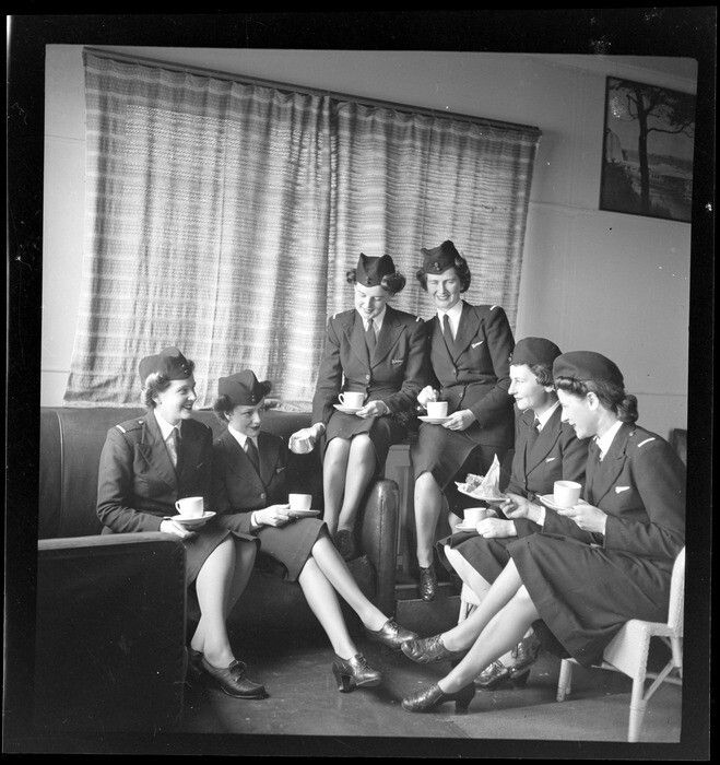 TEAL Tasman Empire Airways Ltd stewardesses, (l to r): Misses [Maynes?], Everand, Woolley, [Martin?] and Paterson sitting on cane chairs and a leather couch drinking cups of tea, in the lounge room at the TEAL building, Mechanics Bay, Auckland. Date: Aug 1946. Photograph taken by Whites Aviation.