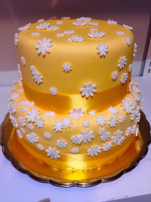 Svatební dort potažený žlutým fondánem, dozdobený bílými fondánovými kytičkami a žlutou saténovou stuhou