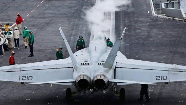 """Auf dem Flugzeugträger """"USS Ronald Reagan"""" steht ein Kampfjet, daneben sind einige Menschen zu sehen. (picture alliance / dpa / Bruce Omori)"""