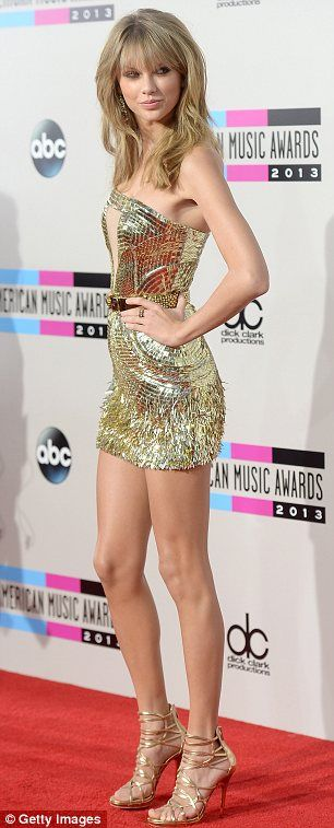 What a transformation: Taylor Swift went for a daring new look in a gold mini-dress and tousled blonde waves at the American Music Awards on...