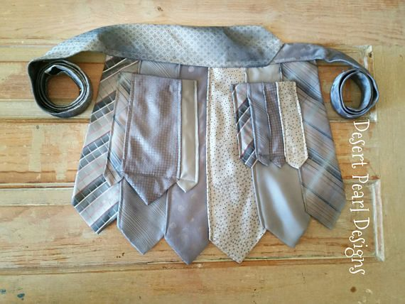 Do you want to stand out at your next event? This one-of-a-kind vendor waitress apron will help you do just that!  This unique vendor apron is made using 7 silk and polyester ties that are sewn into this unique tie apron. These vintage ties of the vendor apron complement each other and have a unique variety of details from geometric, striped, and plaid patterns. The ties that create this waitress apron have various shades of silver grey, soft blue, and soft accent colors. A necktie is used…