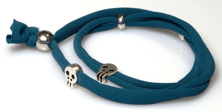 """""""Nice skull"""" è uno dei mille modelli di bracciale in stoffa elasticizzata con piccoli teschi. Vero must della stagione, in realtà i teschi devono la loro fama al designer inglese Alexander McQueen, che se li fece stampare per la prima volta sulla sua sciarpa di chiffon."""