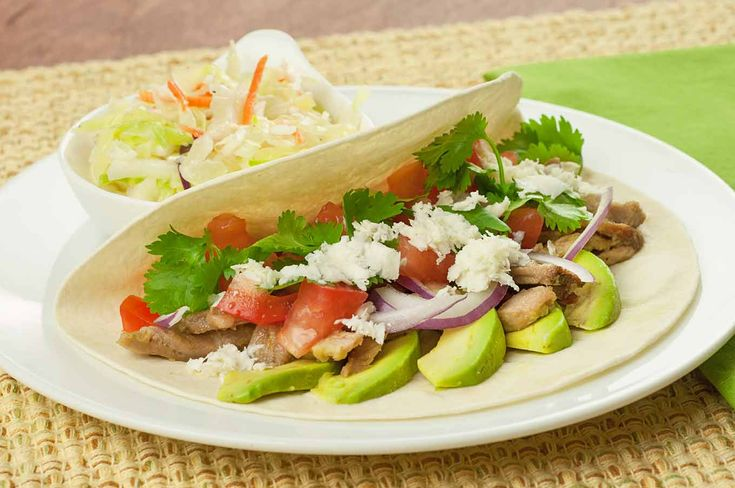 Oven-roasted pulled pork glazed with a mojo-style sauce of olive oil, garlic, orange juice and lime juice combines with avocado, tomatoes, red onion, cilantro and cheese to make these flavorful soft tacos.