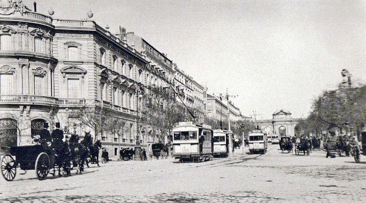 Tráfico por la calle Alcalá, circulando por la izquierda (cambiaría el sentido en 1926). Se observan tranvías eléctricos - los primeros tranvías de tracción animal 'linea Sol-Serrano' se inauguró en Madrid en 1871. Después aparecieron los tranvías de vapor en 1879 -. No se había levantado todavía el Palacio de Comunicaciones, construido sobre uno de los jardines que estaban dentro del antiguo recinto del Parque del Retiro, las obras comenzaron en 1904 y finalizaron en 1917 según un proyecto…