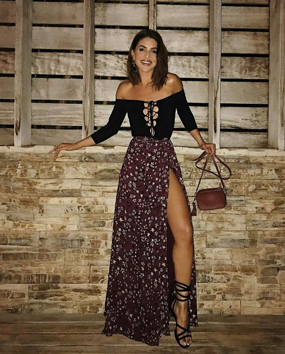 Camila Coelho, blua ombro a ombro preta com decote trançado, saia longa com estampa floral com fenda, sandália de tiras