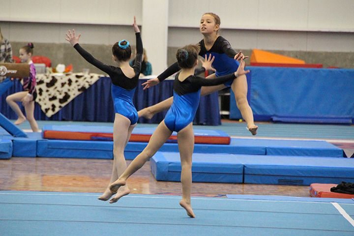 Tyra Green, from left, Veronika Yacovelli and Charli Calvert of North Valley Gymnastics warm up for their floor routines at the Wild West meet in Kamloops.