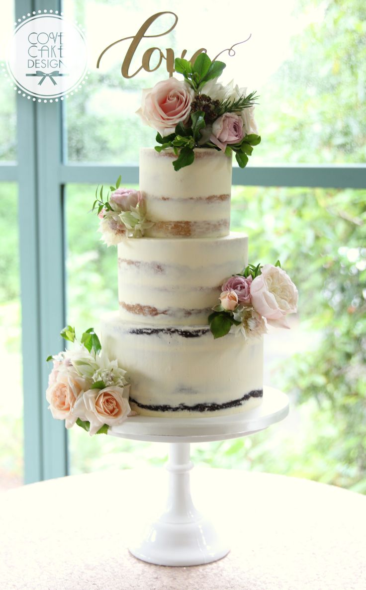 Semi-naked wedding cake with fresh flowers and love topper