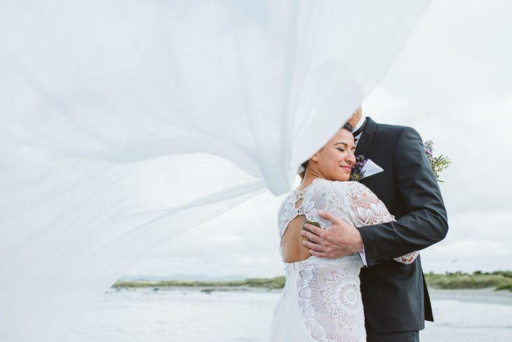 Windy wedding portraits, portraits with veil, veil wedding photo of bride and groom