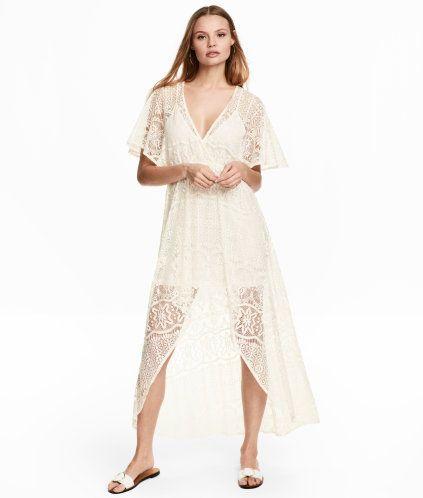 Naturvit. En klänning i genombruten spets med omlottlagt framstycke. Klänningen är v-ringad och har kort fjärilsärm. Avskuren i midjan med smal resår och