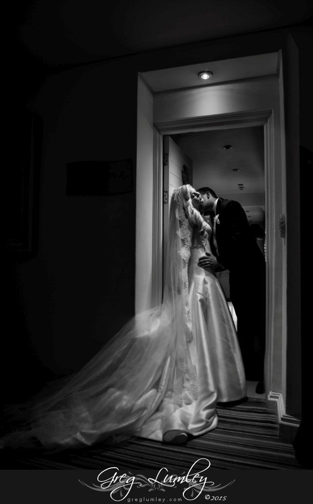 Dramatic contemporary photography.  Groom kissing bride in doorway at The Twelve Apostles Hotel in Cape Town.