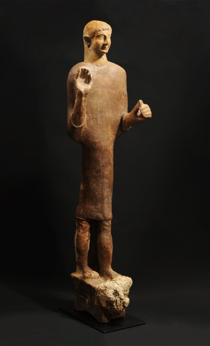 PHOENICIAN LARGE TERRACOTTA STANDING YOUTH. His right hand is raised in an attitude of prayer or greeting; the left once held an implement. Mediterranean marine encrustations. Levant Coast, 6th Century BC. H. 41 in. (104.1 cm.).   Ex Marwan Shehab collection, Beirut, acquired from Asfar & Sarkis, Beirut, in 1964.