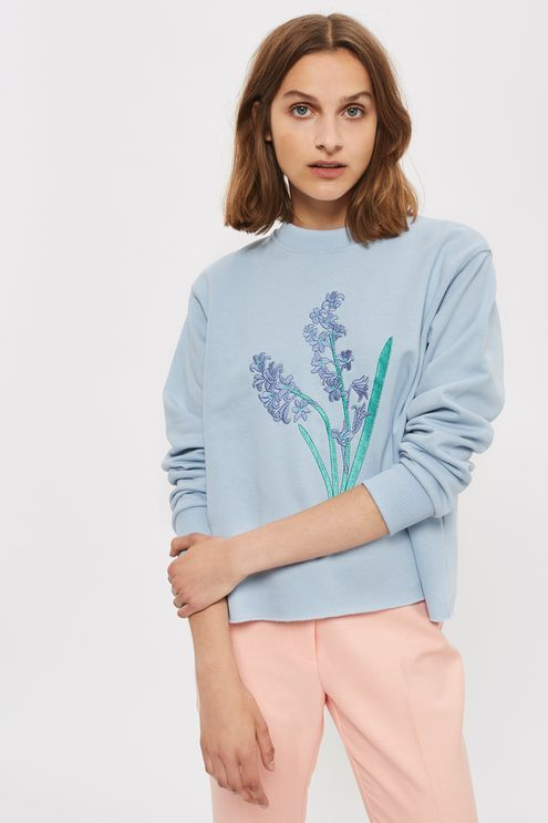 Layering becomes a must when we're given cute options like these. This super-cute sweatshirt by Tee & Cake comes in a summer-ready baby blue hue, complete with large bluebell embroidery to the front and a raw cut off hem. We're styling with pastel trousers for a sugar-sweet finish.
