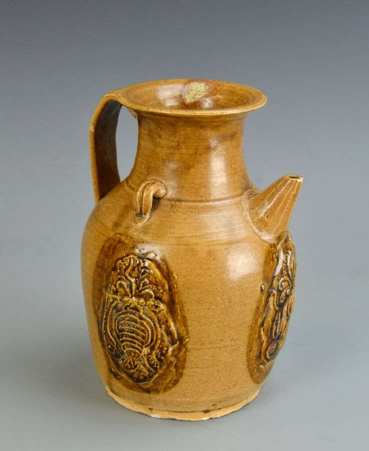 China, Tang Period, Changsha Yao wine pot, with a small spout placed below the neck, and attached panels of decoration. Height 7 in.