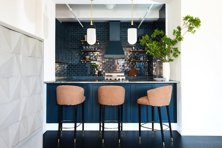 "Finding the right shade of blue for the semi-open kitchen—one that conveyed old-school sophistication but also looked modern—was crucial for both the clients (a young couple with a daughter) and the designers. They eventually settled on Benjamin Moore's matte Navy 1652 for the custom cabinets, and glossy ceramic tiles from Waterworks in a matching shade. ""It's seriously luxe and even a little moody,"" says client Rachel Gerstein. ""Bright white kitchens are great, but that's just not the vibe…"