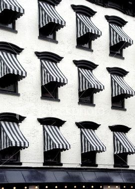 No idea where these awnings are but they sure look crisp & classic | black + white stripes