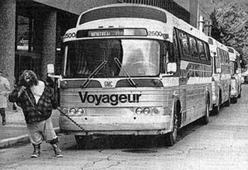 Le Grand Antonio tirant quatre autobus remplis de passagers, rue Sainte-Catherine, à Montréal (1960)