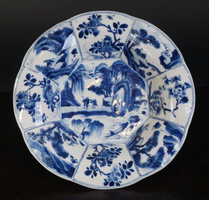 Een zeer mooi antiek blauw witte porseleinen bord - China -eind 17e eeuw ( Kangxi periode )  Een mooi antiek Chinees porseleinen blauw wit bord uit de Kangxi periode 17e eeuw. Gelobd model in lotusbloem vorm. Zeer fraai gedecoreerde landschap met personage decor in het midden en rondom. Erg goed diep blauw kangxi kleur. Zeer fraai geschilderd. Porselein zeer wit van kleur. Zeer exclusief model!Conditie: Zeer goedenkel chip aan achterzijde zie foto's Afmeting: 21 cm diameterVerzendkosten…