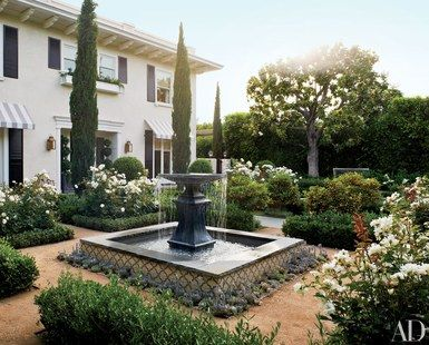 In the entrance courtyard of a Los Angeles home, local firm Modern Floristry designed the Italianate garden, which includes a pair of lead fountains (one is shown) from Authentic Provence | archdigest.com