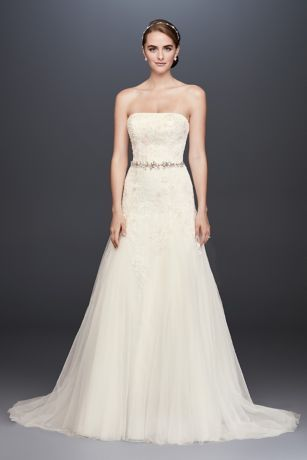 A straight neckline gives this strapless A-line wedding dress a classic profile from the start. Lace appliques trail from the bodice, past the slim grosgrain waistband, and onto the airy, godet-inset