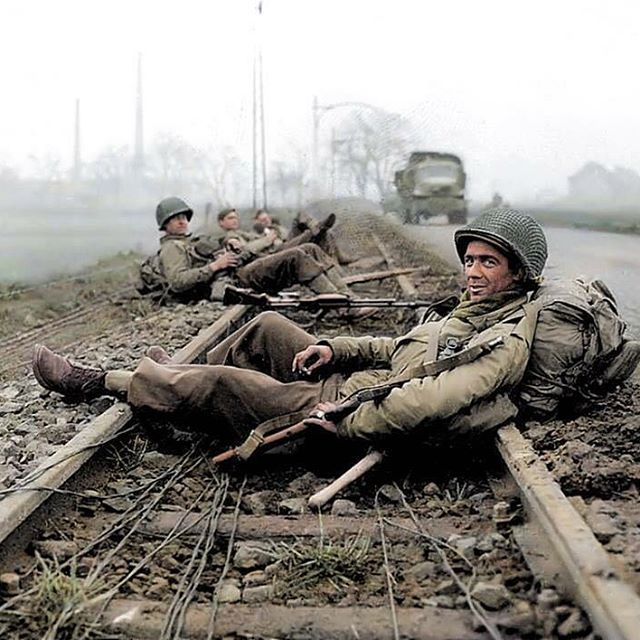 "the_ww2_archives GIs of the 413th Infantry Regiment, 104th Infantry Division ""Timberwolves"", resting on the rail track after combat in Düren, a town in North Rhine-Westphalia, Germany. 21 December 1944. During the Battle of the Bulge, the 104th actively defended its sector near Düren and Merken from 15 December to 22 February 1945. (Colourised by Royston Leonard UK) https://www.facebook.com/pages/Colourized-pictures-of-the-world-wars-and-other-periods-in-time/182158581977012 2016/12/22…"