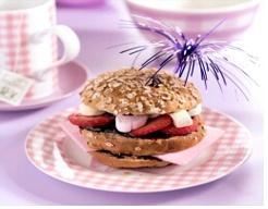 Snijd de mueslibol in drie laagjes en bestrijk de onderste twee lagen royaal met bosvruchtenjam. Leg het kokosbrood op de onderste laag. Leg hierop de middelste laag met de jamkant naar boven en verdeel de aardbeien en marshmallows over deze broodlaag. Bestrijk de onderkant van het kapje met bosvruchtenjam en dek de clubsandwich hiermee af. Snijd de sandwich eventueel in vieren en steek door elk stapeltje een cocktailprikker. mini-bolletjes?