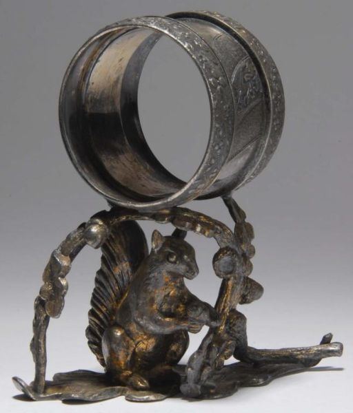 Squirrel with Nut Figural Napkin Ring.  A squirrel with a nut stands on leaf base and is surrounded overhead by an arbor of leaves and acorns on top of which the napkin holder sits. Marked Reed & Barton.