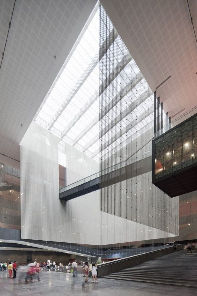 This monumental, massive void that fills the space of the Guangdong Museum in Guangzhou, China feels lightweight and not heavy or solid simply because of the materials utilized. Glass and aluminum combine here to create what feels like the light-filled centerpiece of the museum in which a simple bridge is the only thing to break up that massive void.