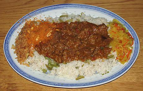 Rendang Pedis, geserveerd met witte rijst, snijboontjes, seroendeng, gebakken uitjes en atjar tjampoer. Bereid door de Happy Chief Cook. Een Indonesisch rundvlees gerecht.