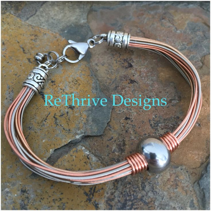 ReThrive Designs: recycled guitar string multi strand bracelet with stainless bead and wire wrapping. Perfect piece for men who love classy guitar string jewelry.