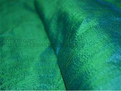 Diese schillernde Dupionseide Gewebe eine brillanten Glanz und Querfäden von Grün und Peacock blau.Das Dual-Ton der beiden Farben ist unter verschiedenen Beleuchtungswinkeln und deutlich, wenn auch...