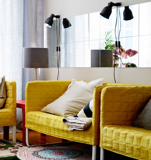 Two IKEA sofas against a wall with a long row of mirror tiles and lamps.