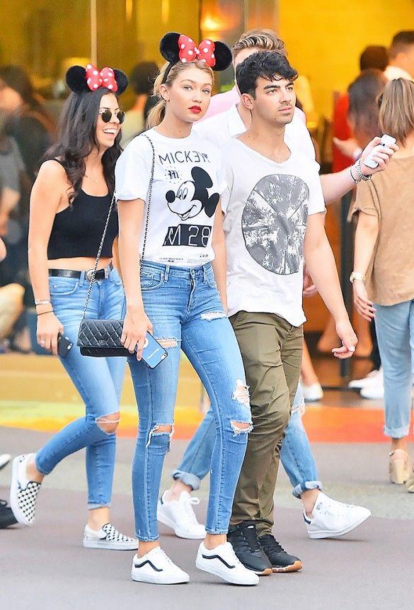 Gigi Hadid wears a graphic t-shirt, distressed skinny jeans, Vans sneakers, a Chanel bag, and mouse ears