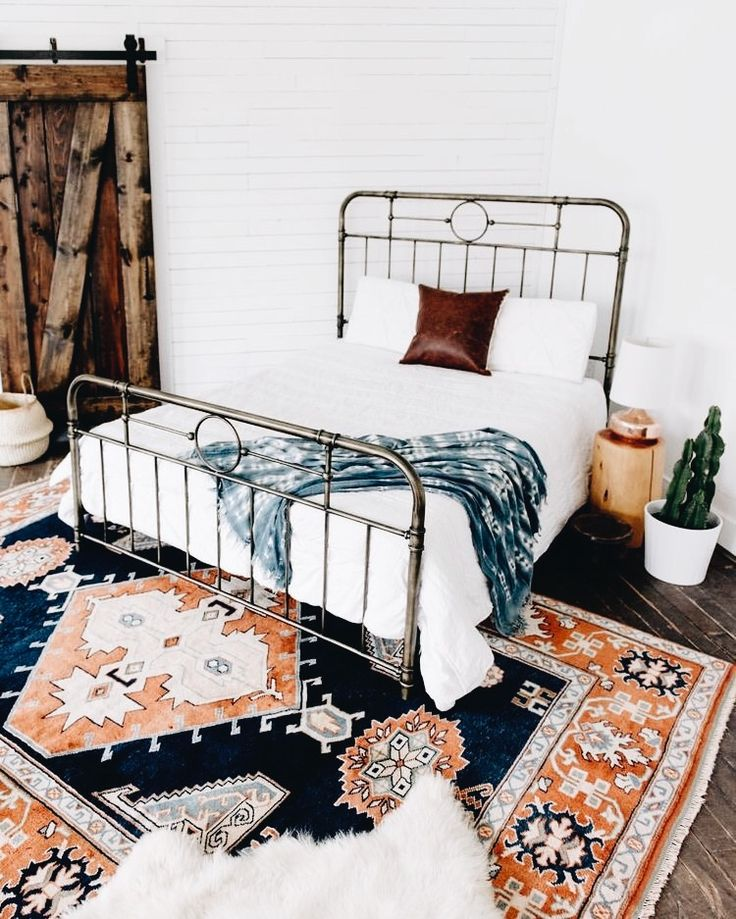 [Beautiful rug and very cool bedside table. The room is strongly bottom-heavy though; they need to carry the color and accessories up the wall. A band of the dark blue around the top of the room would help; two with a narrower band of orange between them would be even better.]