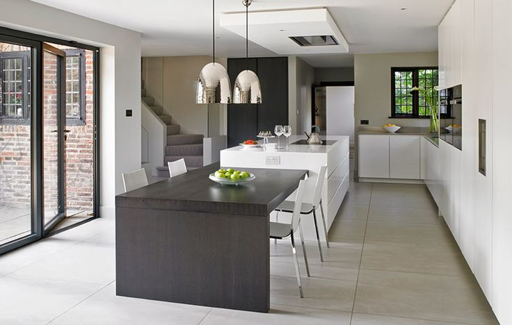 Wimbledon Kitchen Design with sleek white modern cabinets,  island with attached dining table in dark stained oak.